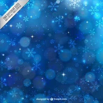 Fundo azul do inverno com flocos de neve