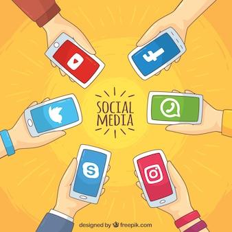 Fundo das mãos que prendem telefones móveis com redes sociais