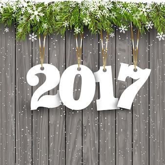 Fundo do ano novo feliz com os números que penduram em um fundo de madeira nevado