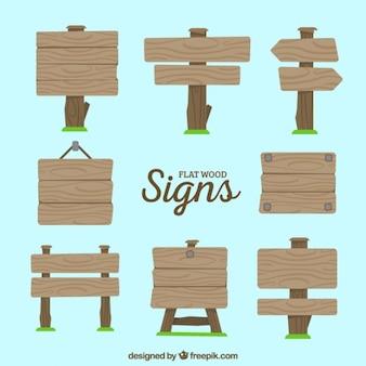 Jogo de sinais de madeira com grama no estilo plano