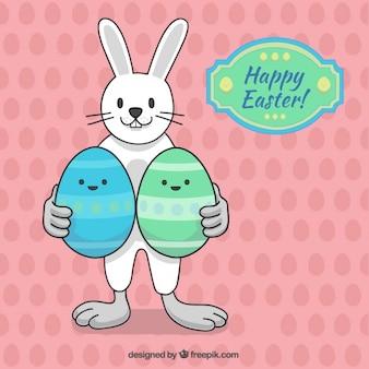 Mão do coelho desenhada com dois ovos de Páscoa