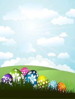 Ovos de Easter coloridos na grama em um fundo da paisagem ensolarada