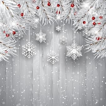 Pendurar flocos de neve com galhos de árvores de prata do Natal em um fundo de madeira