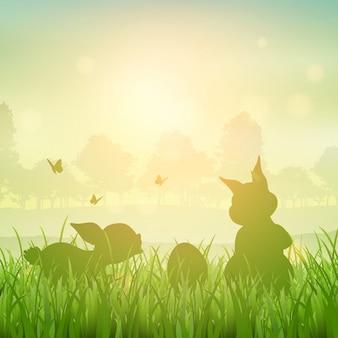 Silhueta de coelhinhos da Páscoa em uma paisagem gramínea