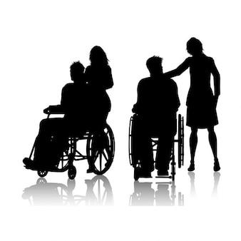 Silhueta de um homem em uma cadeira de rodas com uma mulher