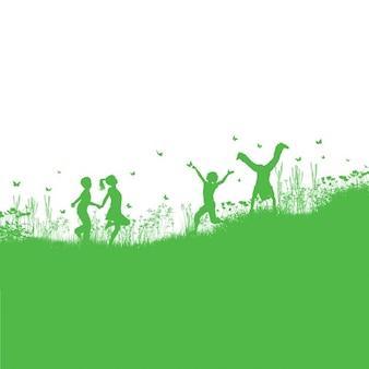 Silhuetas das crianças que jogam na grama e flores