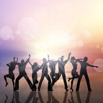 Silhuetas de pessoas dançando em um fundo do sol de verão