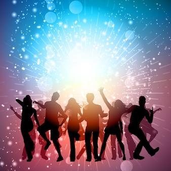Silhuetas de pessoas dançando em um fundo starburst
