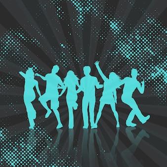 Silhuetas de pessoas que dançam em um fundo de pontos de meio-tom