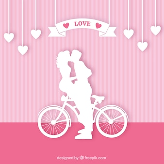 Silhuetas de um casal se beijando em uma bicicleta