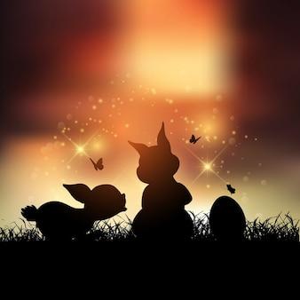 Silhuetas dos coelhos de Páscoa contra um céu do por do sol