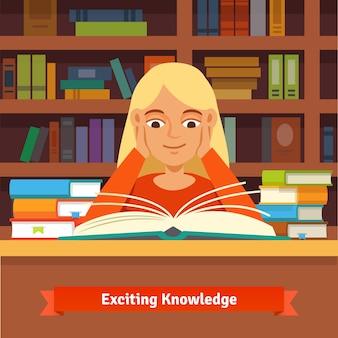 Young blond girl reading book em uma biblioteca