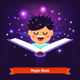 Bambino ragazzo leggendo il libro magico di incantesimi mentre si illumina