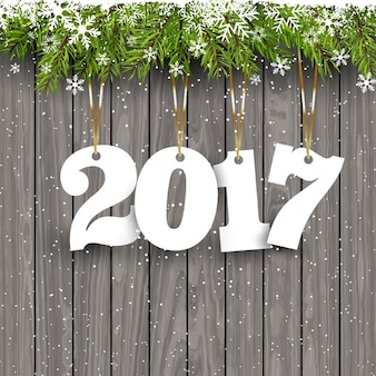 Felice Anno nuovo sfondo con i numeri appesi su uno sfondo di legno innevato