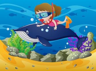 Immersione ragazza con balena sotto il mare