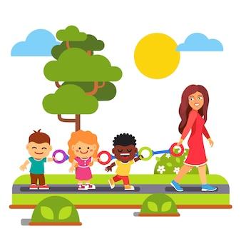Insegnante di scuola materna a piedi con i bambini all'aperto