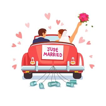 La coppia di nozze sta guidando la macchina per la loro luna di miele