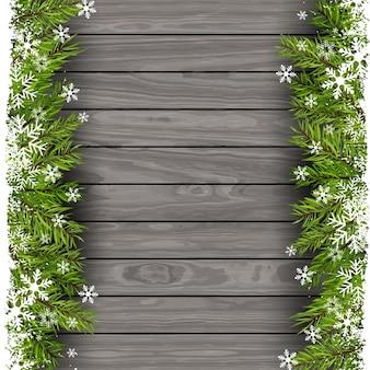 Rami di un albero di Natale su uno sfondo di legno