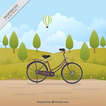 Retro bicicletta in un paesaggio con alberi di sfondo