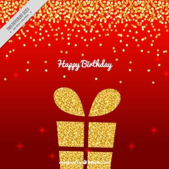 Sfondo rosso con regalo di compleanno d'oro e coriandoli