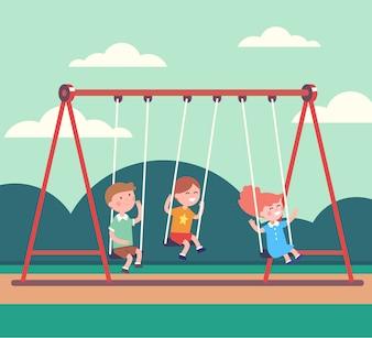 Tre bambini ragazzi e ragazza che oscilla nel parco pubblico