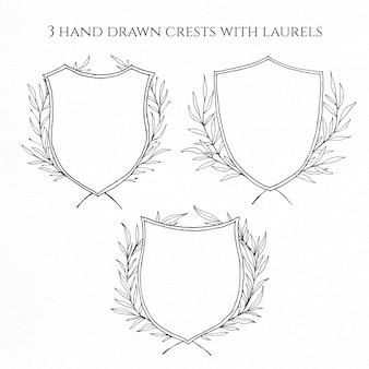 Tre creste disegnate a mano con allori per un design matrimonio