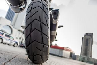 Achterwiel van rode motorfiets in de stadsstraat