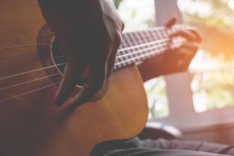 Akoestische gitaargitarist spelen. Muzikaal instrument met uitvoerende handen.
