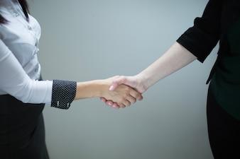 Anonieme vrouwen schudden handen op grijs
