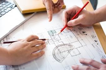 Architecten bespreken aan de tafel met blauwdruk - Close-up op handen en project printen.