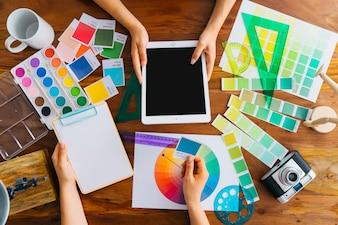 Artiesten met tablet en klembord bij bureau