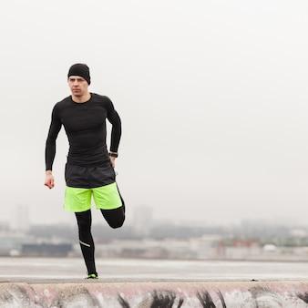 Atleet stretching been op een grijze dag