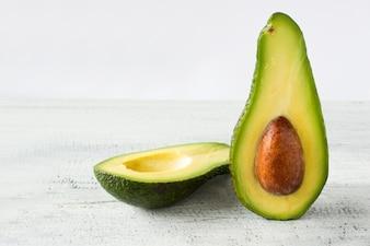 Avocado voedsel achtergrond met verse biologische avocado op oude houten tafel, kopieer ruimte