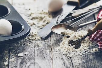 Bakkenconcept keuken koken bestek accessoires voor bakken op houten achtergrond met bloem. Bovenaanzicht. Kookproces. Niemand.