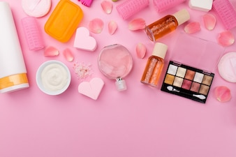 Beauty Spa Feminine Concept. Verschillende Make-up Beauty Care Essentials Cosmetica op Flat Lay Pink Background. Bovenaanzicht. Bovenstaand.