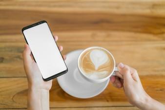 Bedrijfs hand met mobiele telefoon en latte kunst koffie.