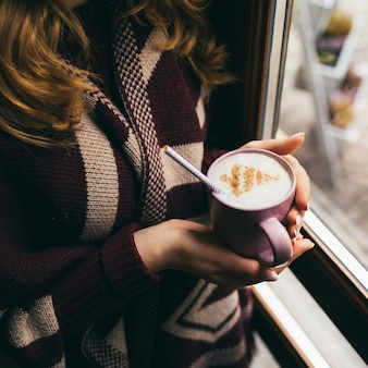 Beker met melk schuim en kerstboom van kaneel in de armen van de vrouw