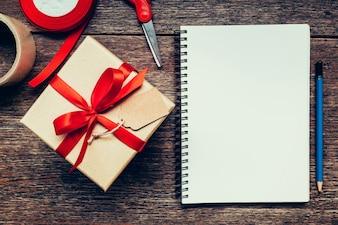 Bekijk hierboven bruine cadeau doos en notitieboekje met label op houten achtergrond met ruimte.