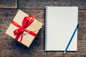Bekijk hierboven bruine cadeau doos en notitieboekje met label op houten achtergrond met space.Vintage geschenkdoos met label op houten achtergrond. Bruin Pakket Op Een Dek.
