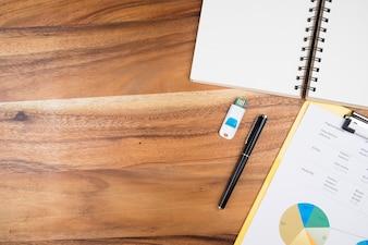 Bekijk van bovenkant van kantoorbenodigdheden en analyseer bedrijfskaart op een achtergrond met houten werktafels.
