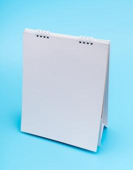 Blanco tabel kalender met pagina's, geïsoleerd op blauwe achtergrond.
