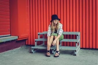 Blond meisje in een hoed. Straatfoto. Een mooi meisje dat casual kleding draagt, lacht mysterieus. Vintage-stijl