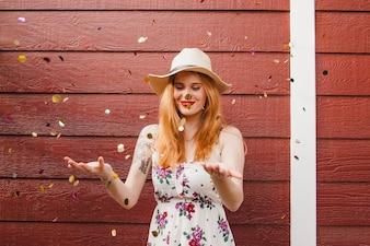 Blond meisje met plezier met confetti