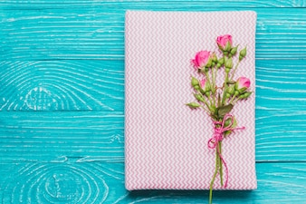 Boek en bloemen op houten oppervlak
