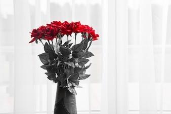 Boeket van verse rode rozen in een vaas.