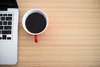 Bovenaanzicht bureau werk laptop en koffiekop notitieblok in huis kantoor.