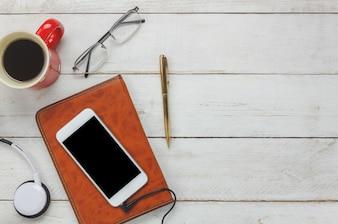 Bovenaanzicht smartphone en koptelefoon met koffiekopje