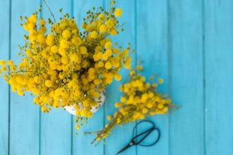 Bovenaanzicht van de blauwe borden met gele bloemen en een schaar