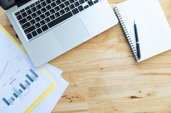 Bovenaanzicht van kantoor houten bureaublad met analysekaart, computer laptop en blanco witte notebook
