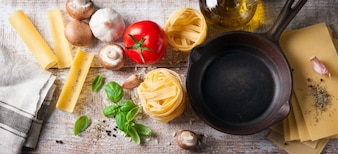 Bovenaanzicht van koekenpan naast verschillende soorten pasta
